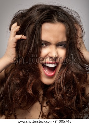 Very frustrated and angry mad woman hands in her hair pulling. Isolated on grey background. - stock photo