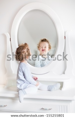 Very funny baby girl with curly hair looking at her reflection in a beautiful white bedroom with a classic dresser with a round mirror - stock photo