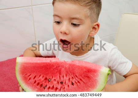 Very handsome cute small blond boy is  eating red ripe juicy watermelon