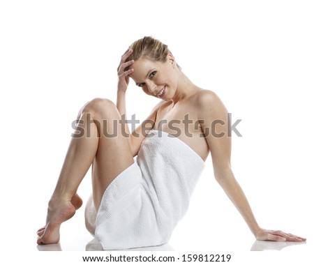 very happy and smiling woman only covered with a white towel in wellness spa style