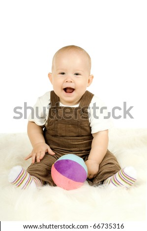 very happy, beautiful,  joy, little kid , lie on stomach and play with ball  on white background - stock photo