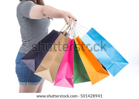 Very happy beautiful young woman in casual clothing with shopping bags, isolated over white background