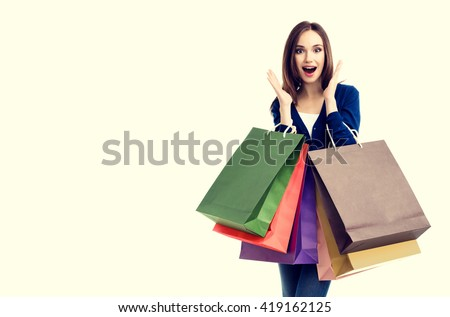 Very happy beautiful young woman in casual clothing with shopping bags, with copyspace for slogan or text message - stock photo