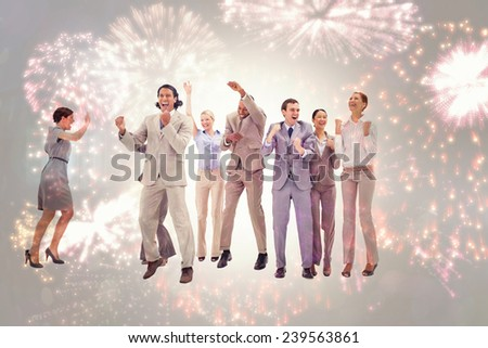 Very happy business people jumping and clenching their fists against colourful fireworks exploding on black background - stock photo