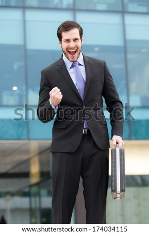 very happy businessman in front of an office building  - stock photo