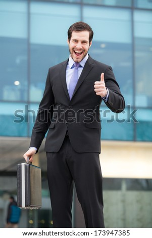 very happy businessman in front of an office building with a briefcase