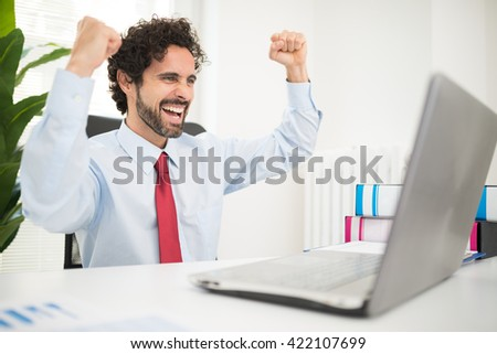 Very happy businessman looking at his computer