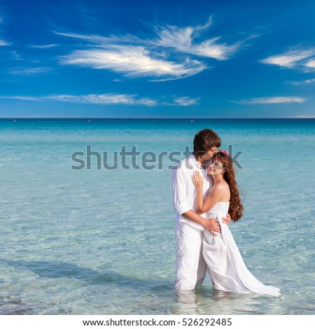 Very happy couple enjoy each other on the beach of blue sea