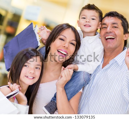 Very happy family shopping and holding bags