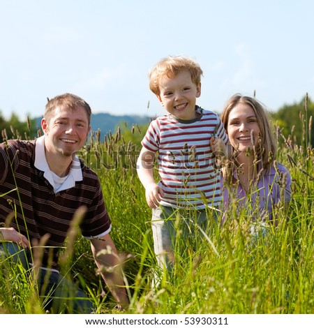 Very happy family with son sitting in a  meadow in the summer sun in front of a forest and hills, they are nearly hidden by the high grass, very peaceful scene - stock photo