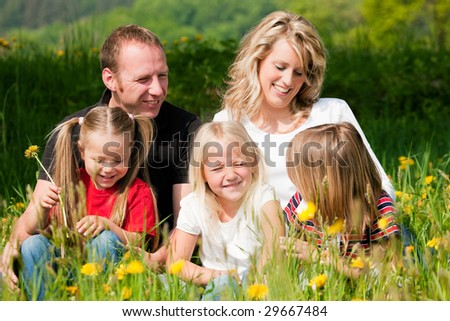 Very happy family with three kids sitting in a meadow with dandelion in the summer sun - stock photo