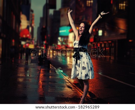 Very happy female walking in a NYC street with her hands rised - stock photo