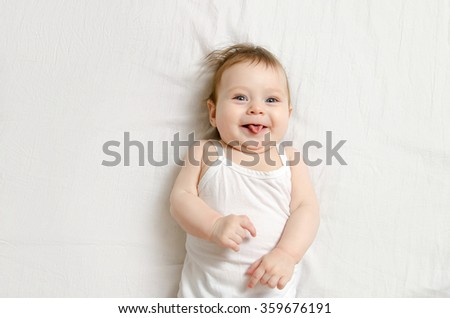 Very happy laughing baby in white body suit lying on his back on the white sheet and show his tongue.  - stock photo