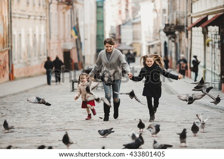 Very happy mom with her daughters dispersing pigeons