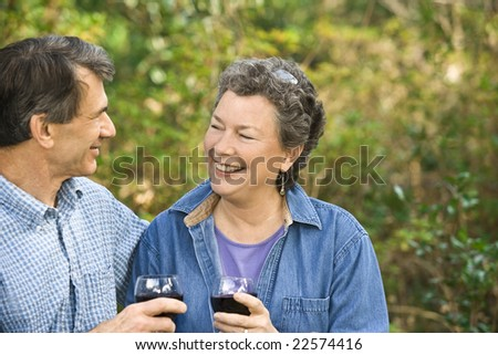 Very happy senior couple laughing and toasting to each other's health and happiness. - stock photo