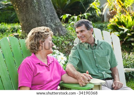 Very happy smiling mature couple relaxing outdoors, holding hands. - stock photo