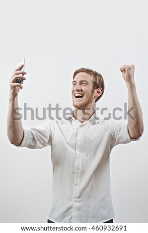 Very Happy Smiling Young Adult Man in White Shirt Looking at His Mobile Phone, Arms Raised, Fist Pumped