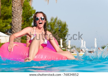 very happy woman on pink air bed in swimming pool - stock photo