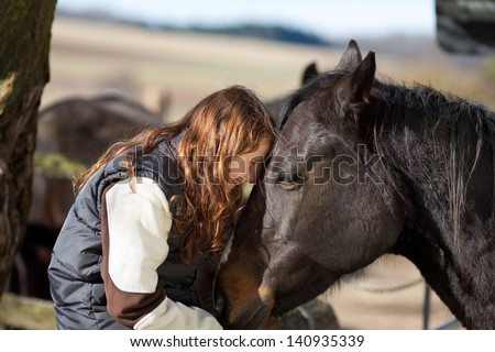 Very happy young girl sitting in the wooden paddock fence pets her dark bay horse