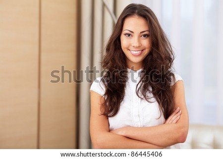 Very happy young woman standing with arms crossed - stock photo