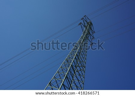 Very high electricity pylon during the sunny day with bright sun and blue sky  - stock photo