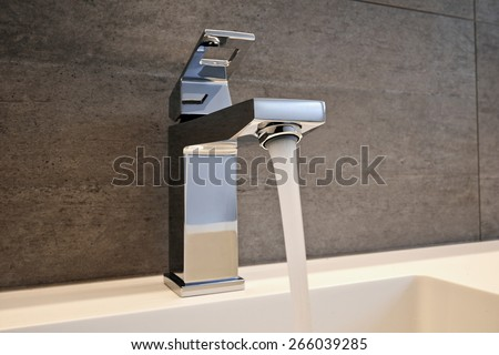 Very high end faucet, sink, and counter in a luxury bathroom - with water split on - stock photo