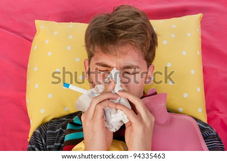Very ill man is laying in his bed with warm water bottle and thermometer while blowing his nose - stock photo