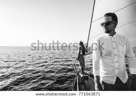 Very interesting black and white photo on which a guy stands in the foreground and a girl in the background, they are on a yacht and enjoy beautiful views