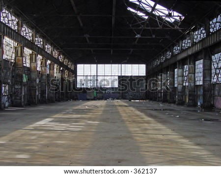 Very large, abandoned, rusty old warehouse, machine shop or factory. Sun shines through Broken windows. Even with glass, trash. graffiti, and debris are on the floor, the place is mostly clear. - stock photo