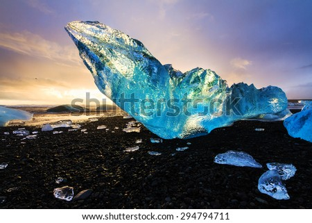 Very large and beautiful chunk of ice at the beach at Jokulsarlon, Iceland, at sunset in winter - stock photo
