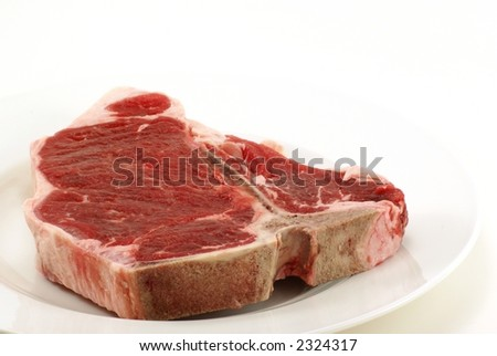 Very large and thick, fresh, juicy uncooked tbone steak on white plate with copy space. - stock photo