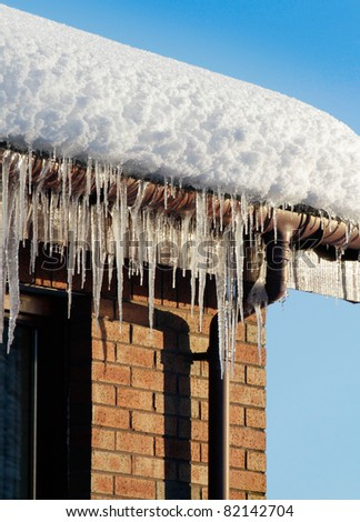 Very large icicles on the edge of a typical brick house in the UK