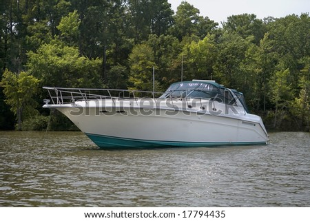 Very large luxury speed boat anchored next to shore. - stock photo