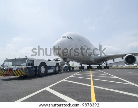 Very large wide-body airplane being towed at an airport - stock photo