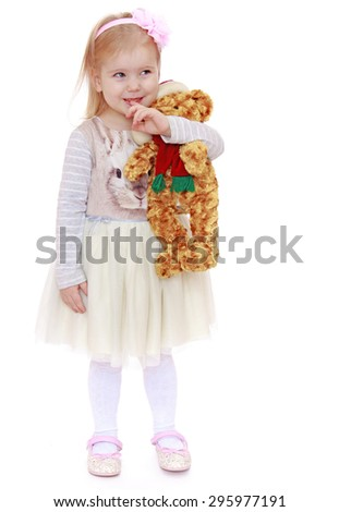 Very little blond Caucasian girl dressed in a beautiful white dress holding a stuffed toy - isolated on white background - stock photo