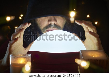 Very low key portrait of hooded man with eyes covered reading fortune on bright crystal ball, surrounded by candle light. - stock photo