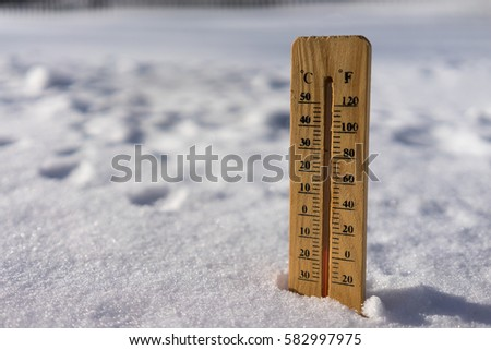 very low temperature thermometer in snow country sunny chill winter metering tree under zero