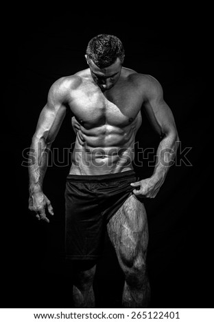 very muscular handsome athletic man on black background, naked torso, black-and-white - stock photo