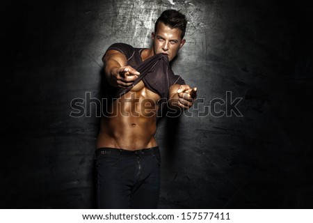 Very muscular handsome sexy guy posing on dark background. - stock photo