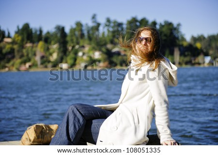 Very natural and beautiful girl on vacations posing in a windy morning at the lake - stock photo