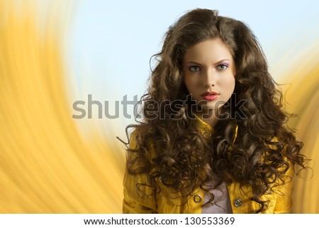 very nice and sexy fashion brunette girl with curly hair in a fantasy yellow and baby blue background - stock photo