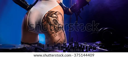 Very nice ass with a tattoo of the girl - DJ, standing near the remote