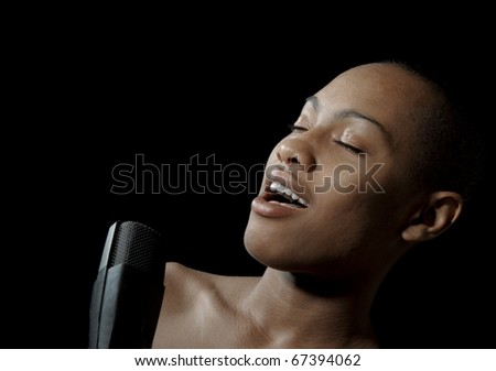 Very nice image of a singer with microphone on black - stock photo