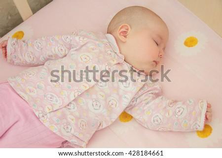 Very nice sweet baby sleeping in crib - stock photo
