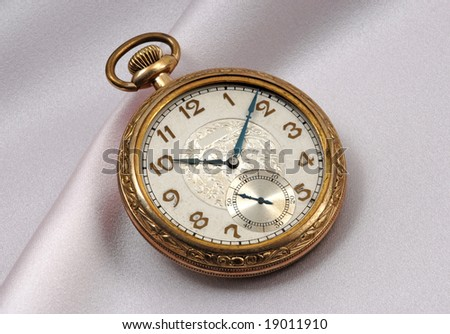 Very old and beautiful gold pocket watch on satin fabric - stock photo