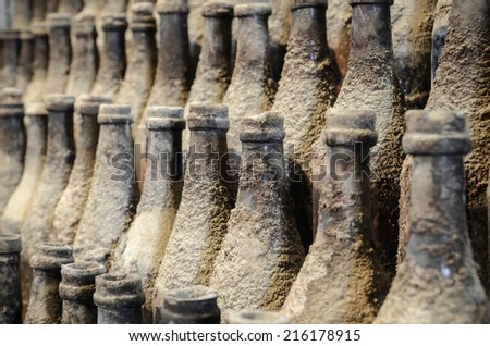 Very old and dusty bottles stacked in warehouse - stock photo