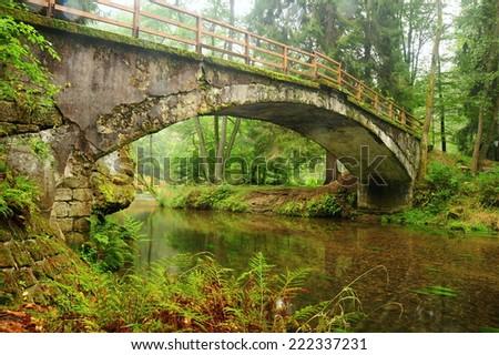 Very old bridge over the river Kamenici in Czech Switzerland - stock photo