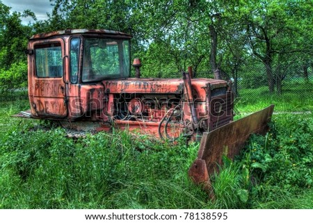 Very old bulldozer leaved on field, by HDR. - stock photo