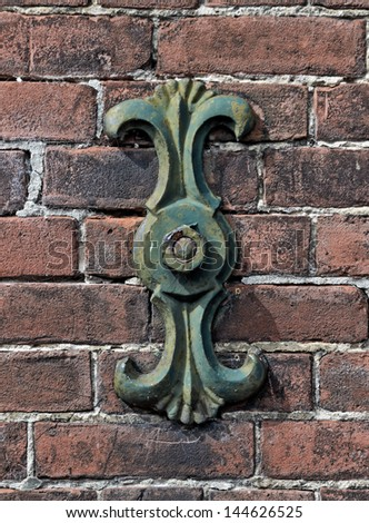 Very old cast iron cramp on brick wall. - stock photo