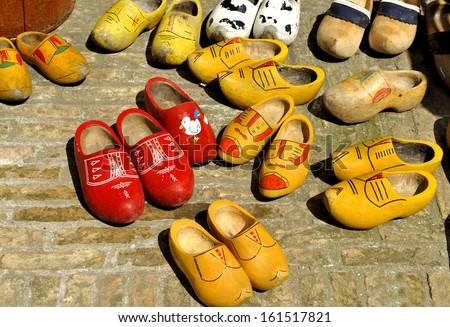 Very old Colored Dutch wooden shoes - clogs at a flea market - stock photo